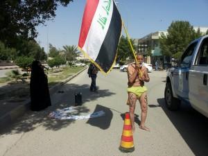 يظهر في الصورة مواطن عراقي يخلع ملابس احتجاجا على عدم تعيين ابنته